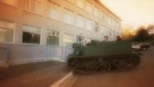 A screen grab of a small army tank with a driver and two people on a street