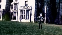 A screenshot of the mannequin-soldier posing by a castle.