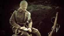 A screen shot of the mannequin-soldier sitting in the trench and writing a letter.
