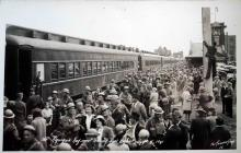 A black and white photograph of a large crowd of both soldiers and civilians at a train station