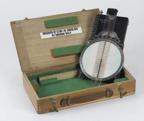 A small wooden box with a plastic and metal calculator inside.