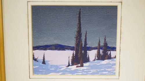 An image of a small, framed painting of a snowy landscape with a stand of conifers in the foreground.
