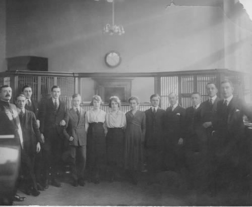 A black and white photograph of Byron Cooper Sisler posing with fellow bank  employees.