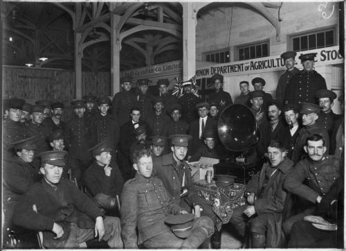 A black and white photograph of Canadian soldiers sitting around a phonograph.