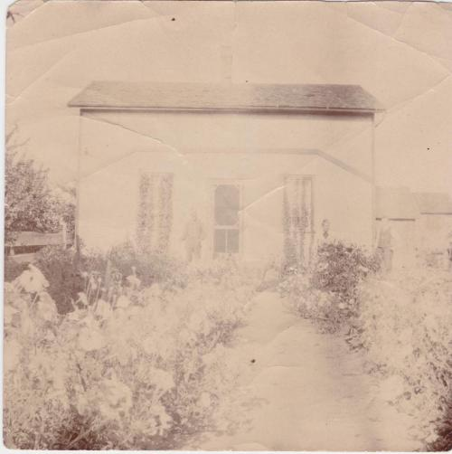 A photograph of a farmhouse with four people outside.