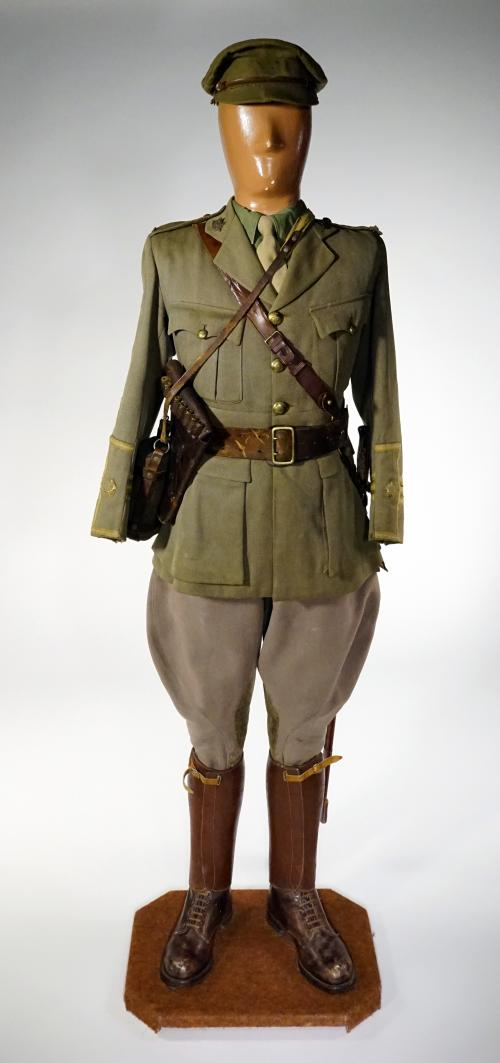 A mannequin is wearing a green khaki cap, a sword, a leather side arm holster and tunic; its cuffs are embellished with three stripes.