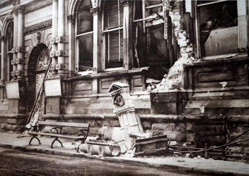A photograph of the bombed Royal Hotel with debris on the street.