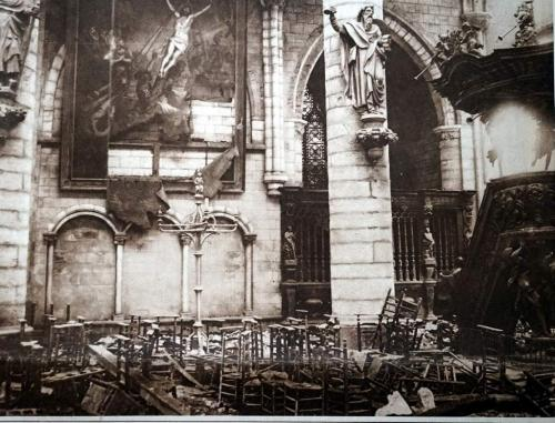 A photograph of the interior of a bombed-out church with a partially  destroyed painting of Christ.