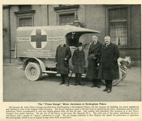 A black-and-white photograph of four people, including young Prince George, posing with a motorized ambulance.