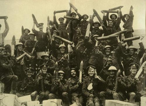 A black-and-white image of a large group of Canadian soldiers happily hoisting   shells in the air.