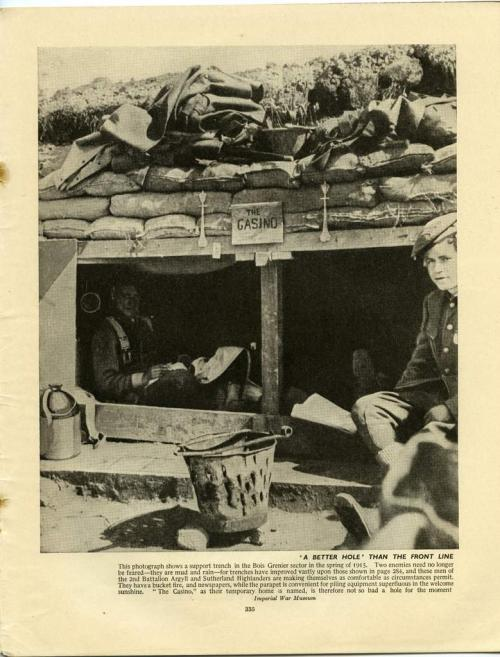 A black-and-white photograph of two soldiers sitting inside a well-constructed dugout in a trench.