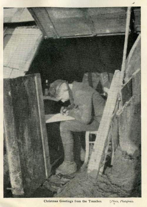 A black-and-white photograph of a soldier sitting inside a trench writing a letter.