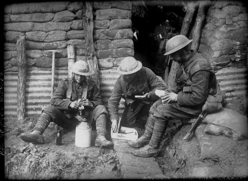 Three Canadian soldiers are sitting in a trench opening their parcels and  enjoying a bite to eat.