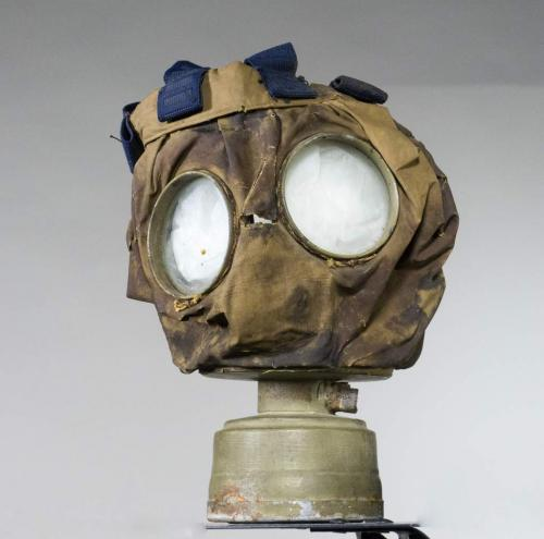 A canvas gas mask with goggle eyes and a small, metal canister on the bottom.
