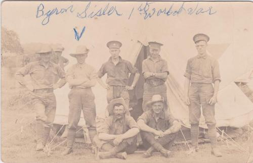 A black-and-white photograph of a group of soldiers posing in front of a tent.