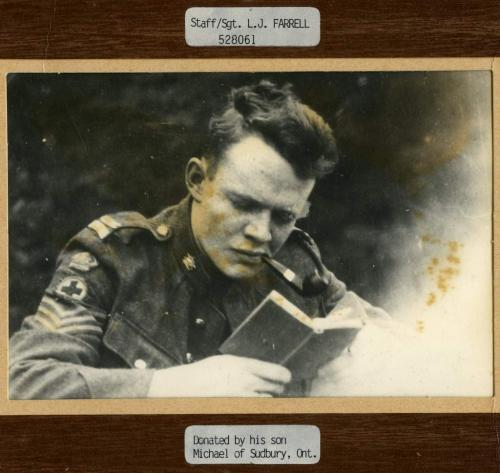 A black-and-white photograph of medic Staff Sergeant Leslie Farrell reading   a book.