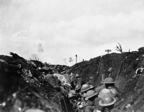 A black-and-white image of soldiers in a trench with shrapnel bursting in background.