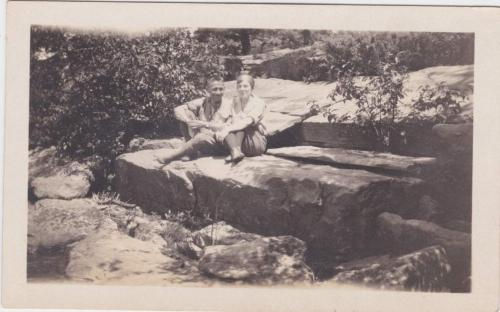 A black-and-white photograph of Byron and Mildred sitting on large rocks.