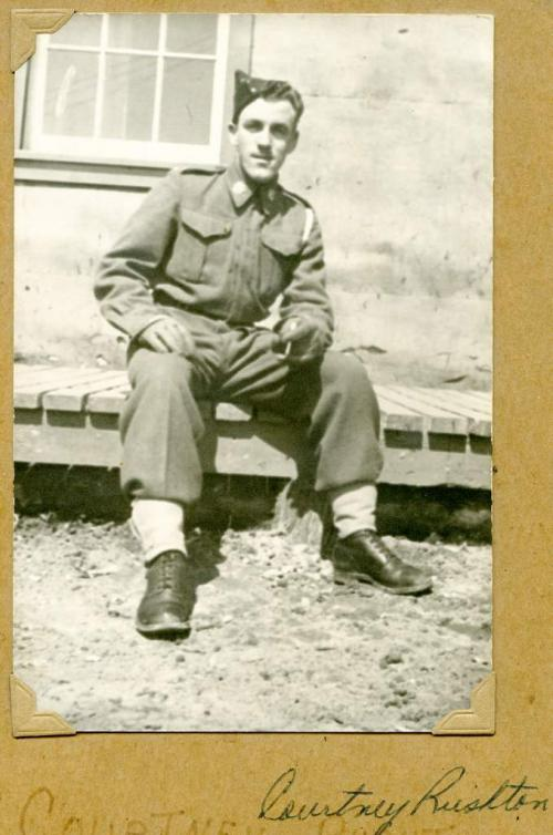 A black-and-white photograph of a young soldier in uniform sitting on a wooden sidewalk.