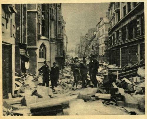 A black-and-white photograph of a civilian and several soldiers in a bombed-out city.