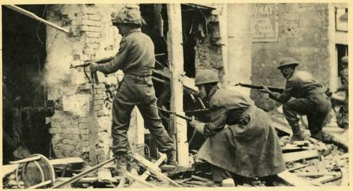A black-and-white photograph of soldiers with guns searching bombed-out buildings.