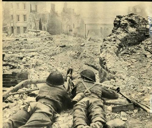 A black-and-white photograph of two soldiers lying with a PIAT at the end of a bombed-out street.