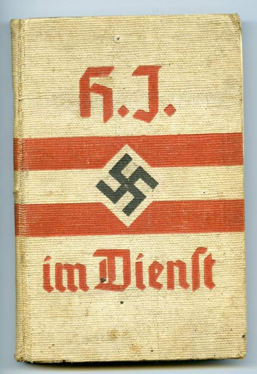 A beige hardcover manual with red writing, two red stripes and a black  swastika in the centre.