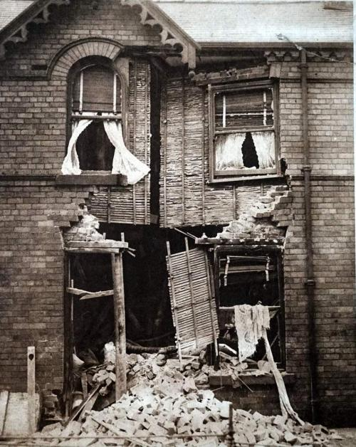 A photograph of a bombed two-story brick building with its front doors blown out.