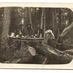 A black-and-white photograph of five men having a meal near a prospector's tent in the woods.