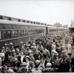 A black-and-white photograph of many soldiers boarding a train