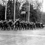 A black and white photograph of a group of soldiers marching, lead by a  military brass band.
