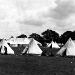 A black and white photograph of two groups of soldiers by white military tents  at Camp Niagara.