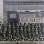 A black and white photograph of a large group of soldiers posing outside a  recruiting station.