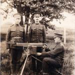 A photograph of two soldiers standing at attention behind a machine gun  manned by a sitting soldier.