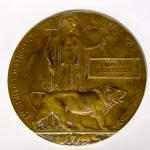 "A bronzed round plaque inscribed with the words ""He died for freedom and  Honour""."