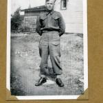 A black-and-white photograph of a soldier in uniform posing in front of a house.