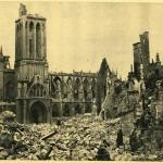 A black-and-white photograph of a church and a bombed-out street.
