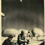 A black-and-white photograph of two soldiers washing with large balloons floating in background.